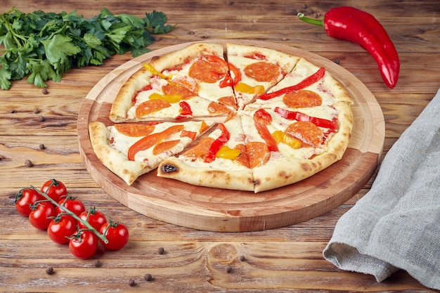 Pizza met vlees, groenten en champignons, houten achtergrond