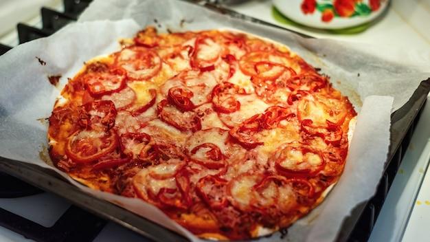 Pizza met vlees, kaas en tomaten