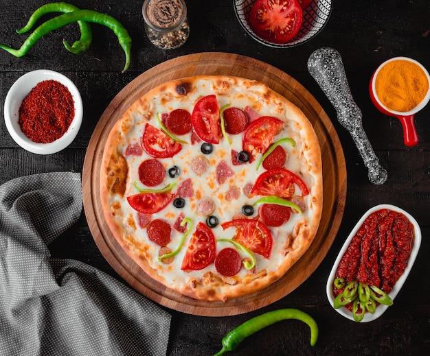 Pizza met worst tomaten en olijven bovenaanzicht