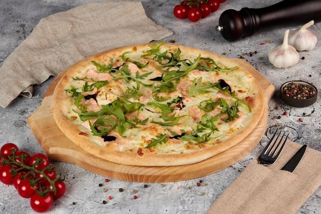 Pizza met zalm en rucola op houten bord, grijze achtergrond