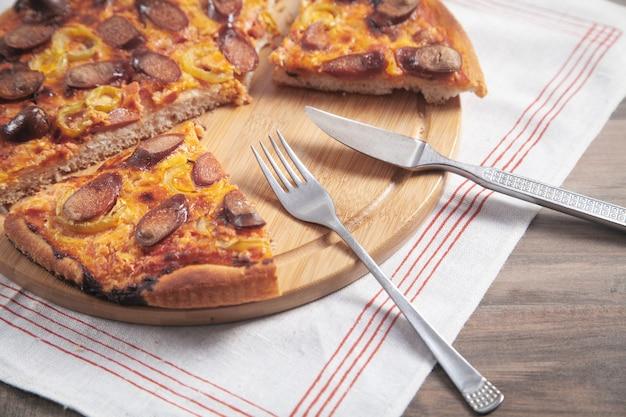 Pizza op cirkelbord met een vork en mes.