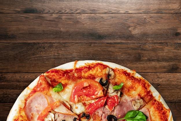 Pizza op houten met ham, olijven, tomaten en groene basilicum