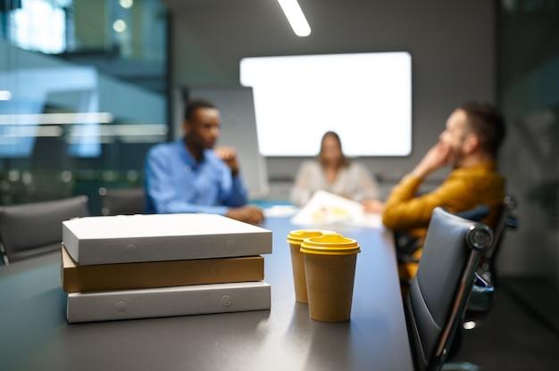 Pizza op tafel, zakenlunch in it-kantoor