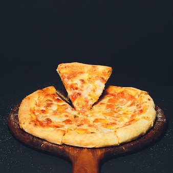 Pizza pepperoni, oregano op een zwarte tafel