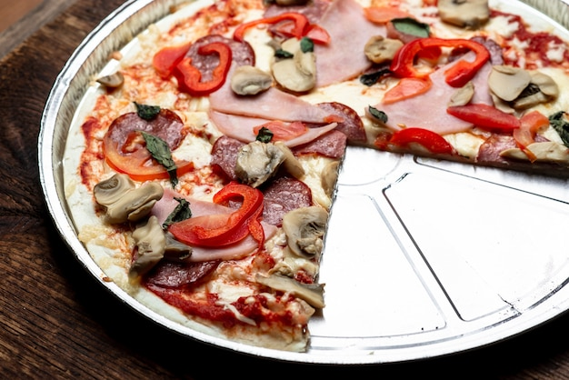Pizza rand close-up op een houten achtergrond. spek, salami, champignons en greens.