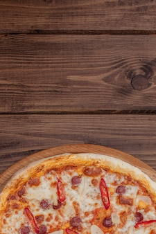 Pizza restaurant menu - delicious spicy pizza with sausages and chili pepper. pizza op rustieke houten tafel met ingrediënten
