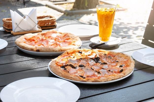 Pizza serveren met ham prosciutto in een straatrestaurant. italiaans eten en duindoornthee voor de lunch op een terras op een zonnige dag