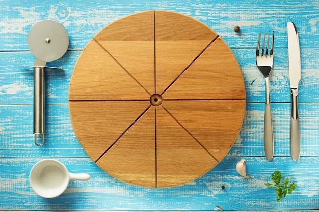 Pizza snijplank en keukengerei aan houten tafel