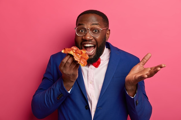 Pizza tijd concept. positieve mannelijke kantoormedewerker of ondernemer in pak houdt een groot stuk pizza vast, werpt de handpalm op, heeft een goede eetlust