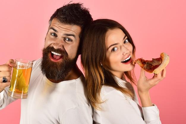 Pizza tijd. fast food. man met bier en vrouw pizza eten. romantisch paar eten. daten. gelukkige familie tijd. verliefde paar genieten van lekkere pizza. geïsoleerd op roze achtergrond.