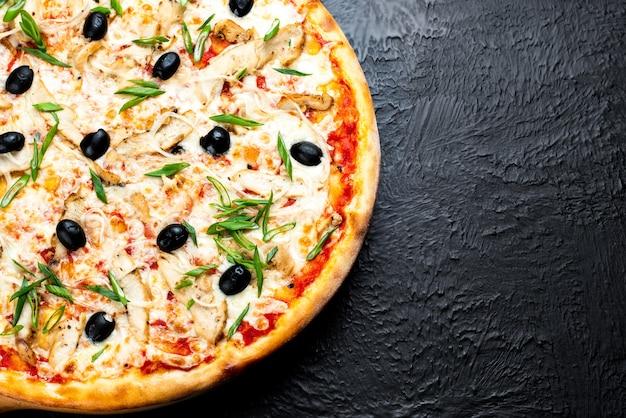 Pizza venetië op een zwarte achtergrond, op basis van tomaten met mozzarella, gegrilde kip, olijven, groen en ui op een houten standaard