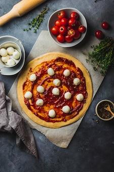 Pizza voorbereiding. rauwe pizza. rol het volkoren deeg uit op bakplaten met diverse ingrediënten voor het koken van peper, mozzarella, tomaat, tomatensaus, tijm en deegroller.