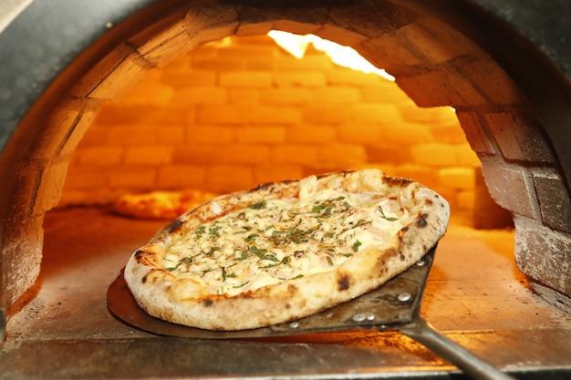Pizza zetten in de houtoven