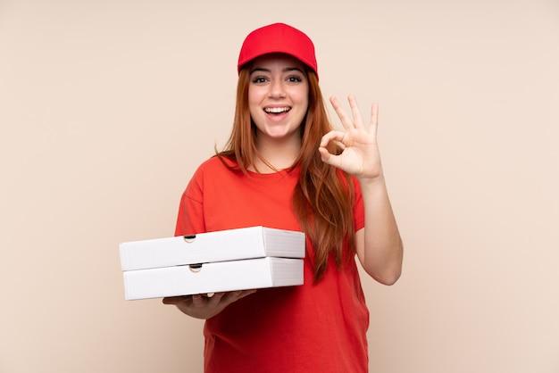 Pizzabezorgende tienervrouw die een pizza houden die een ok teken met vingers tonen