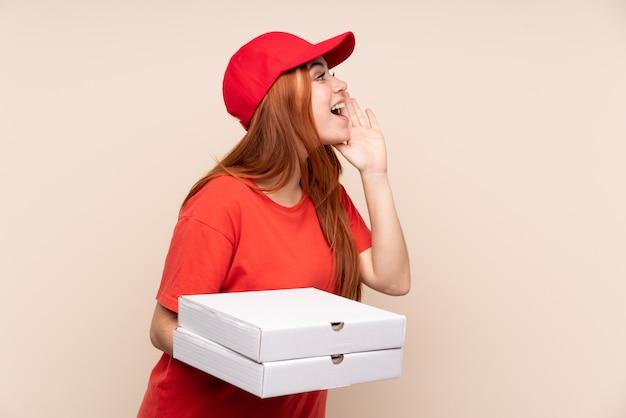 Pizzabezorgende tienervrouw die een pizza houden schreeuwend met wijd open mond
