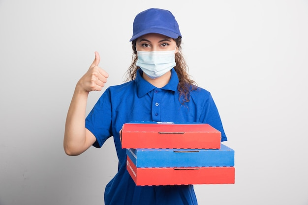 Pizzabezorger die drie dozen met medisch gezichtsmasker vasthoudt en duim op wit laat zien