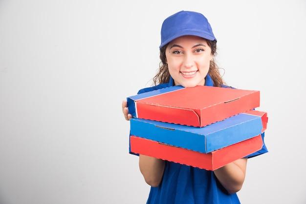 Pizzabezorger die drie dozen op witte achtergrond houdt. hoge kwaliteit foto