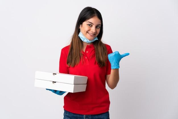 Pizzabezorger die een pizza houdt die op wit wordt geïsoleerd dat naar de kant wijst om een product te presenteren