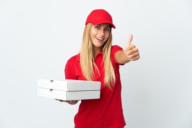 Pizzabezorger die een pizza houdt die op witte muur met omhoog duimen wordt geïsoleerd omdat er iets goeds is gebeurd