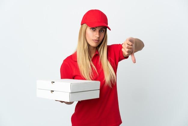 Pizzabezorger die een pizza houdt die op witte muur wordt geïsoleerd die duim met negatieve uitdrukking toont