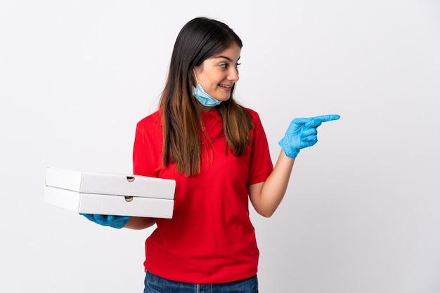 Pizzabezorger die een pizza houdt die op witte muur wordt geïsoleerd die naar de kant wijst om een product te presenteren