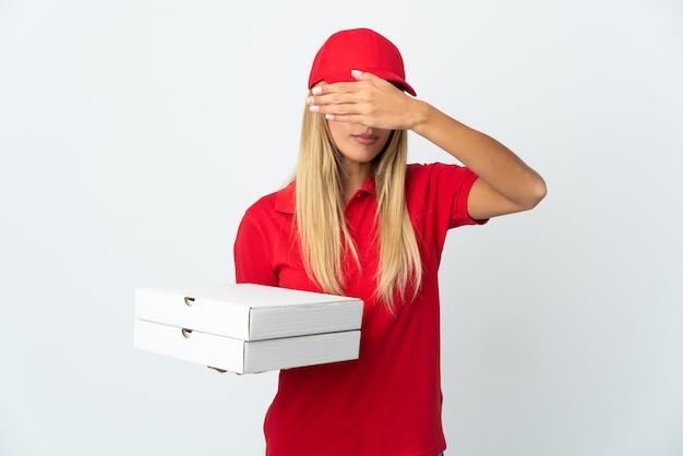 Pizzabezorger die een pizza houdt die op witte muur wordt geïsoleerd die ogen behandelt door handen. ik wil niets zien