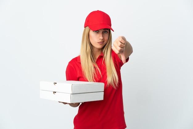 Pizzabezorger die een pizza op wit houdt die duim met negatieve uitdrukking toont