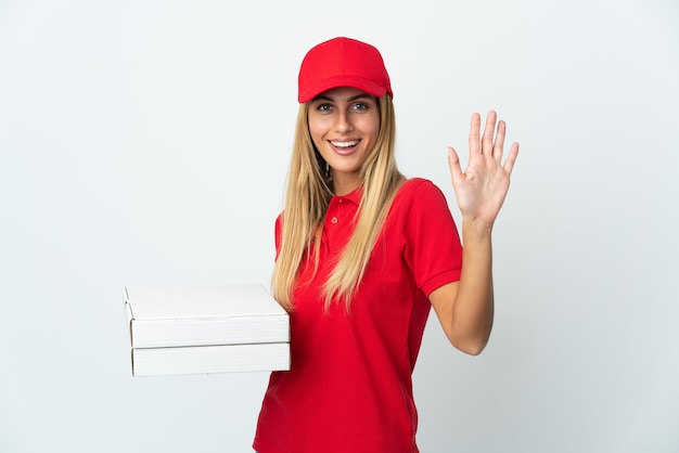 Pizzabezorger die een pizza op wit houdt die met hand met gelukkige uitdrukking groeten
