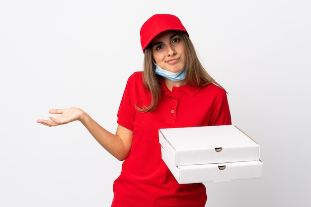 Pizzabezorger die een pizza vasthoudt en beschermt tegen het coronavirus met een masker over geïsoleerde witte muur die twijfelt terwijl ze de schouders optilt
