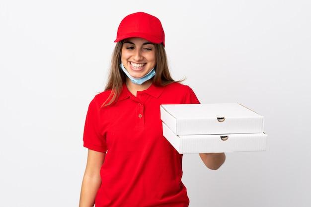 Pizzabezorger die een pizza vasthoudt en beschermt tegen het coronavirus met een masker over geïsoleerde witte muur met gelukkige uitdrukking