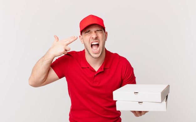 Pizzabezorger die er ongelukkig en gestrest uitziet, zelfmoordgebaar maakt een pistoolteken met de hand, wijzend naar het hoofd