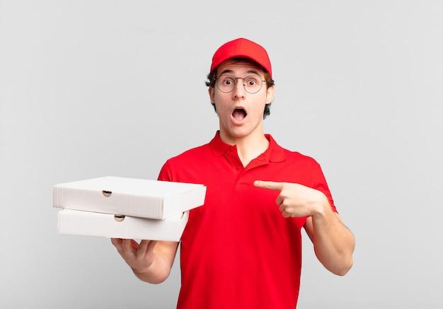 Pizzabezorger die geschokt en verrast kijkt met wijd open mond, wijzend naar zichzelf