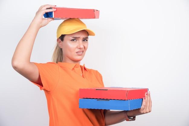 Pizzabezorger die pizzadoos op haar hoofd op witte achtergrond zet.