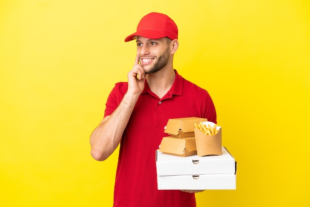 Pizzabezorger die pizzadozen en hamburgers ophaalt over een geïsoleerde achtergrond en een idee denkt terwijl hij opkijkt
