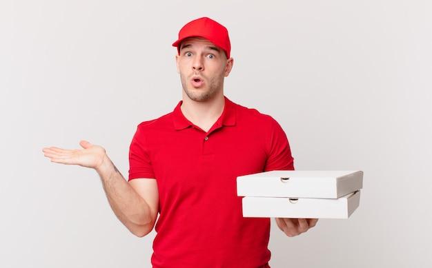Pizzabezorger die verrast en geschokt kijkt, met open mond terwijl hij een object vasthoudt met een open hand aan de zijkant
