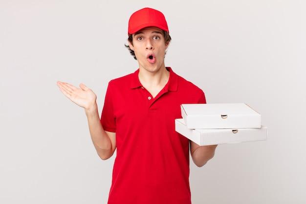 Pizzabezorger die verrast en geschokt kijkt, met open mond terwijl hij een voorwerp vasthoudt