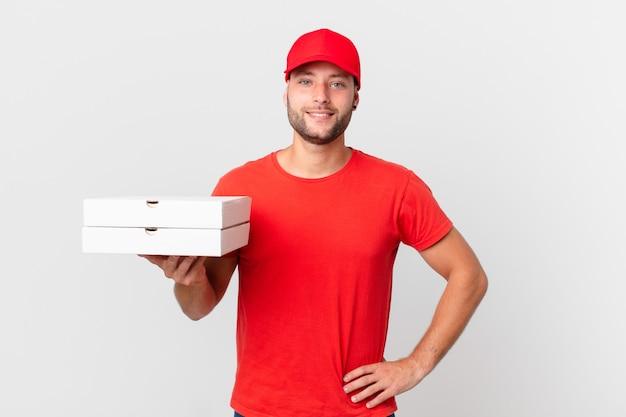 Pizzabezorger die vrolijk lacht met een hand op de heup en zelfverzekerd