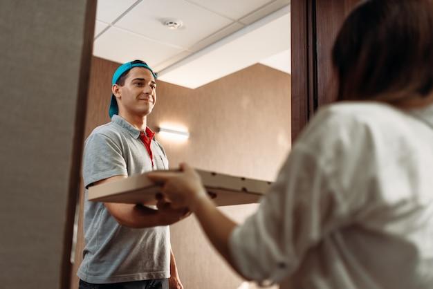 Pizzabezorger geeft kartonnen doos aan vrouwelijke klant voor de deur en levert service. koerier van pizzeria en vrouw binnenshuis