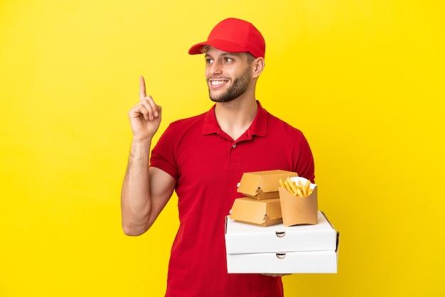 Pizzabezorger haalt pizzadozen en hamburgers op over een geïsoleerde achtergrond en wijst op een geweldig idee