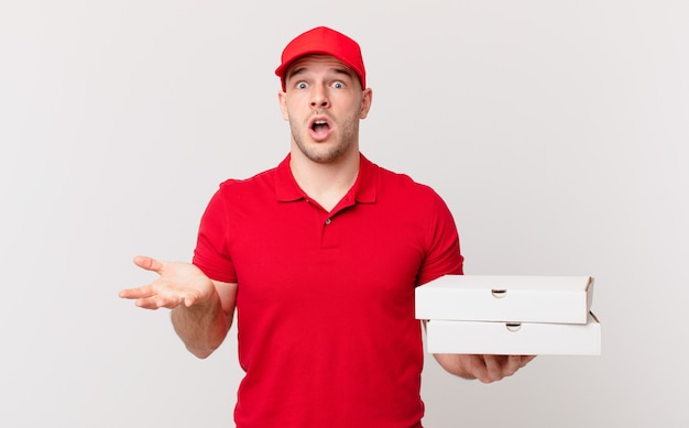 Pizzabezorger met open mond en verbaasd, geschokt en verbaasd met een ongelooflijke verrassing