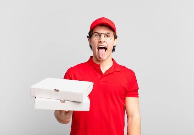 Pizzabezorger met vrolijke, zorgeloze, rebelse houding, grappen maken en tong uitsteken, plezier maken