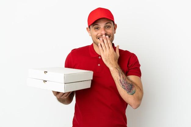 Pizzabezorger met werkuniform die pizzadozen ophaalt over een geïsoleerde witte muur, blij en glimlachend die de mond bedekt met de hand