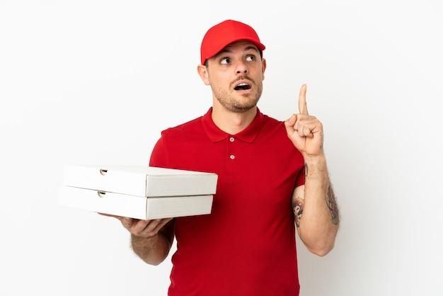 Pizzabezorger met werkuniform die pizzadozen ophaalt over een geïsoleerde witte muur, denkend aan een idee met de vinger omhoog