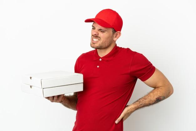 Pizzabezorger met werkuniform die pizzadozen ophaalt over een geïsoleerde witte muur die lijdt aan rugpijn omdat hij moeite heeft gedaan