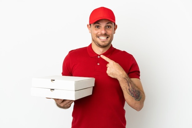 Pizzabezorger met werkuniform die pizzadozen ophaalt over geïsoleerde witte muur met verrassende gezichtsuitdrukking