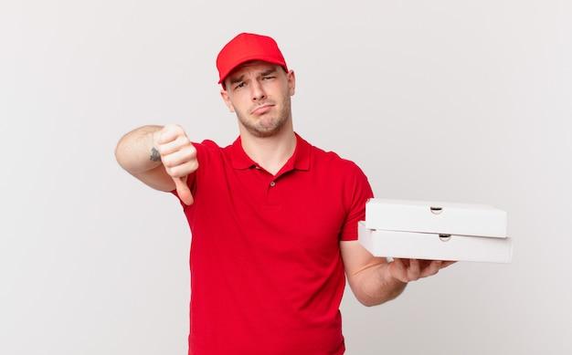 Pizzabezorger voelt zich boos, boos, geïrriteerd, teleurgesteld of ontevreden, duimen naar beneden met een serieuze blik