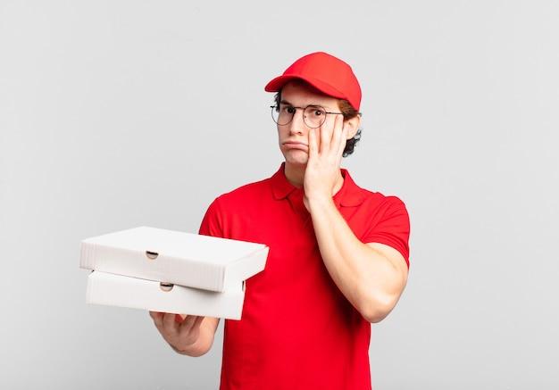Pizzabezorger voelt zich verveeld, gefrustreerd en slaperig na een vermoeiende, saaie en vervelende taak, gezicht met de hand vasthoudend
