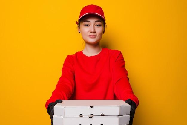 Pizzabezorger vrouw met drie dozen geïsoleerd op gele muur