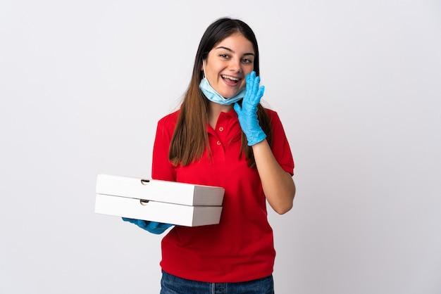 Pizzabezorger vrouw met een pizza geïsoleerd op wit schreeuwen met wijd open mond