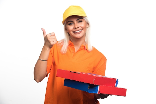 Pizzabezorger vrouw met pizza op witte achtergrond geven duimen omhoog gebaar. hoge kwaliteit foto